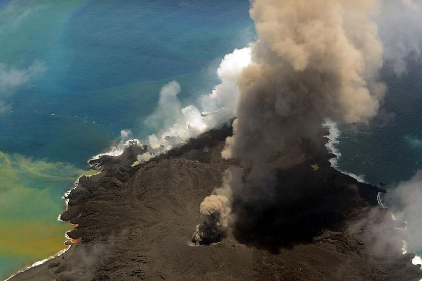 This handout picture taken by Japan Coast Guard on July 23, 2014 shows the newly created islet and Nishinoshima island, which are conjoined with erupting lava at the Ogasawara island chain, 1,000 kilometres south of Tokyo. A smouldering islet off Jap