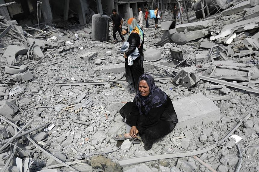 A Palestinian woman reacts at seeing destroyed homes in the northern district of Beit Hanun in the Gaza Strip during an humanitarian truce on July 26, 2014. -- PHOTO: AFP