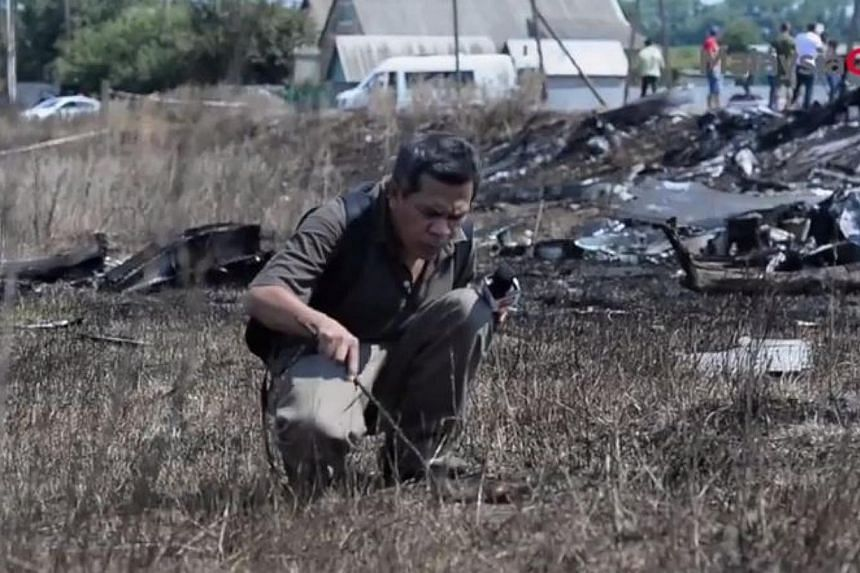 As Malaysia bemoans the lives lost when a missile hit Flight MH17 above eastern Ukraine this month, a Malaysian reporter did the unthinkable: Poking a burnt object believed to be human skin at the crash site for the camera.-- PHOTO: MALAYSIA GA