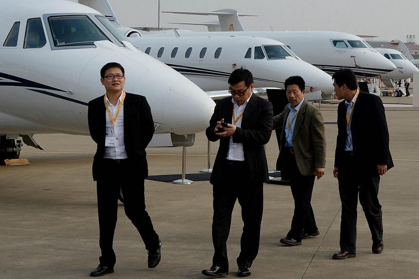 Chinese businessmen walking past private business jets for sale during the Asian Business Aviation Conference and Exhibition at the Shanghai Hongqiao airport. The top one percent of households in Communist-ruled China control more than one third of t