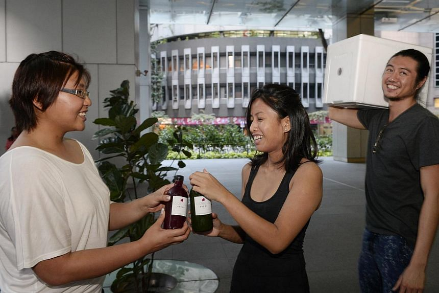 Bank analyst Lee Jiamin (left) gets her juice-cleansing products from Gorilla Press' Valerie Oei (centre), 32, and Ong Weiquan (right), 32, who deliver them to her office in Anson Road. -- ST PHOTO: MARK CHEONG