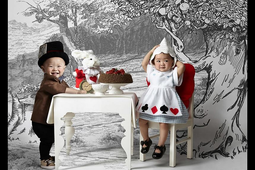 Ms Johanna Thean's newborn daughter, Jodi Huang, dressed as Snow White and Ms Vanessa Ong's twins, Gerick and Glenise Tan (both above) as the Mad Hatter and Alice from Alice In Wonderland when they were a year old. -- PHOTO: VIVIEN NG