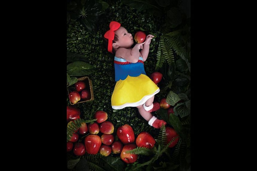 Ms Johanna Thean's newborn daughter, Jodi Huang (above), dressed as Snow White and Ms Vanessa Ong's twins, Gerick and Glenise Tan as the Mad Hatter and Alice from Alice In Wonderland when they were a year old. -- PHOTO: VIVIEN NG