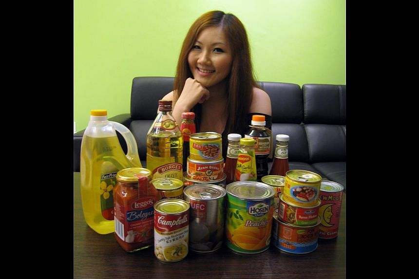E-commerce manager Luisa Lai (above) with the canned goods, sauces and cooking oil she gets from FairPrice Online. She still visits the supermarket to buy fresh ingredients and will shop online more frequently if the minimum spending for free deliver