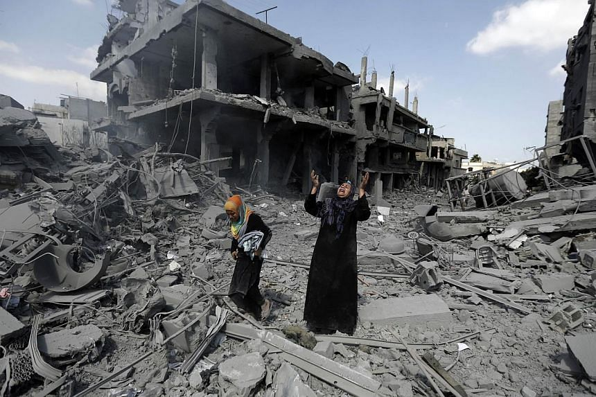 A Palestinian woman pauses amid destroyed buildings in the northern district of Beit Hanun in the Gaza Strip during an humanitarian truce on July 26, 2014. -- PHOTO: AFP