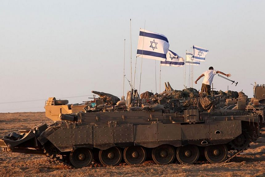 Israeli soldiers work on their an armoured personnel carrier (APC) as they are stationed along the border between Israel and the Hamas-controlled Gaza Strip on July 26, 2014. Israel said on Sunday it was extending a lull in its devastating milit