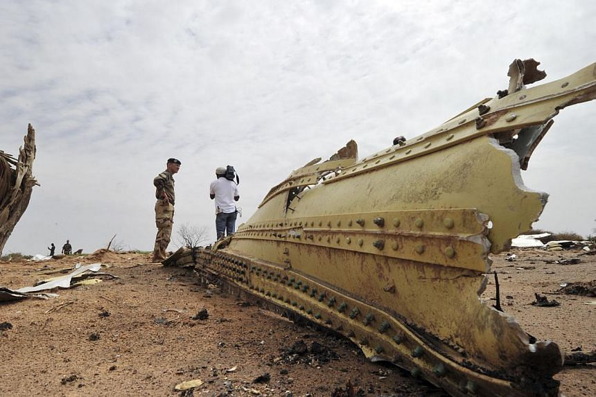 A French soldier and a journalist look at debris of the Air Algerie Flight AH 5017 scattered at the crash site in Mali's Gossi region, west of Gao, on July 26, 2014.French investigators on Sunday, July 27 scoured through the debris of a shatter