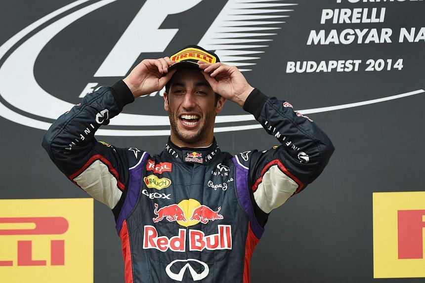 Red Bull Racing's Australian driver Daniel Ricciardo celebrates his victory on the podium after the Hungarian Formula One Grand Prix at the Hungaroring circuit in Budapest on July 27, 2014. -- PHOTO: AFP
