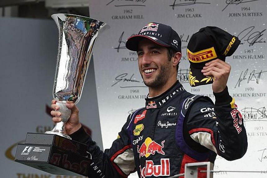 Red Bull Racing's Australian driver Daniel Ricciardo celebrates on the podium after the Hungarian Formula One Grand Prix at the Hungaroring circuit in Budapest on July 27, 2014.  -- PHOTO: AFP