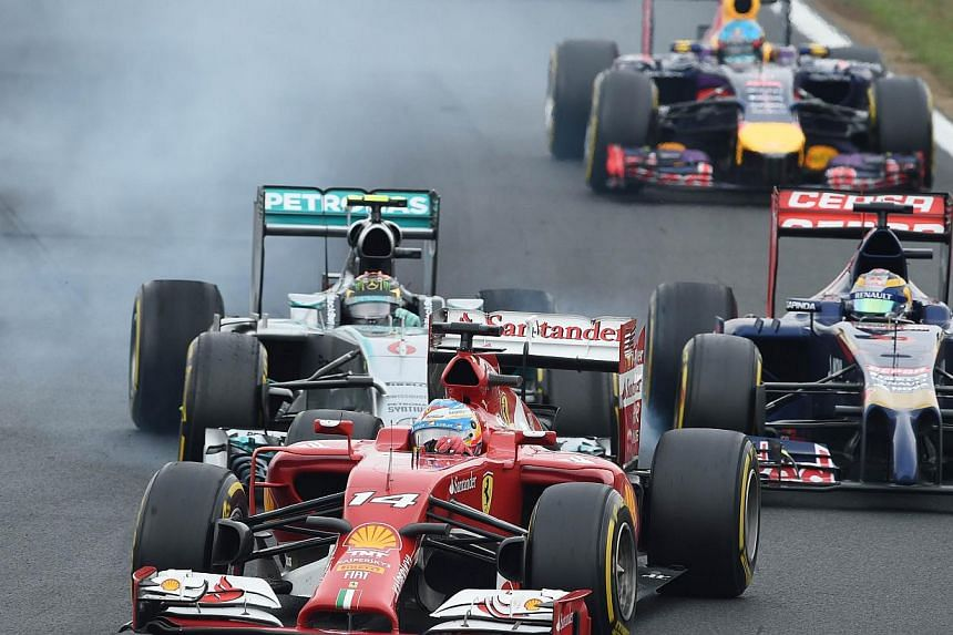 Scuderia Ferrari's Spanish driver Fernando Alonso (front) drives ahead of Mercedes' German driver Nico Rosberg (left) and Red Bull Racing's German driver Sebastien Vettel (right) during the Hungarian Formula One Grand Prix at the Hungaroring circuit