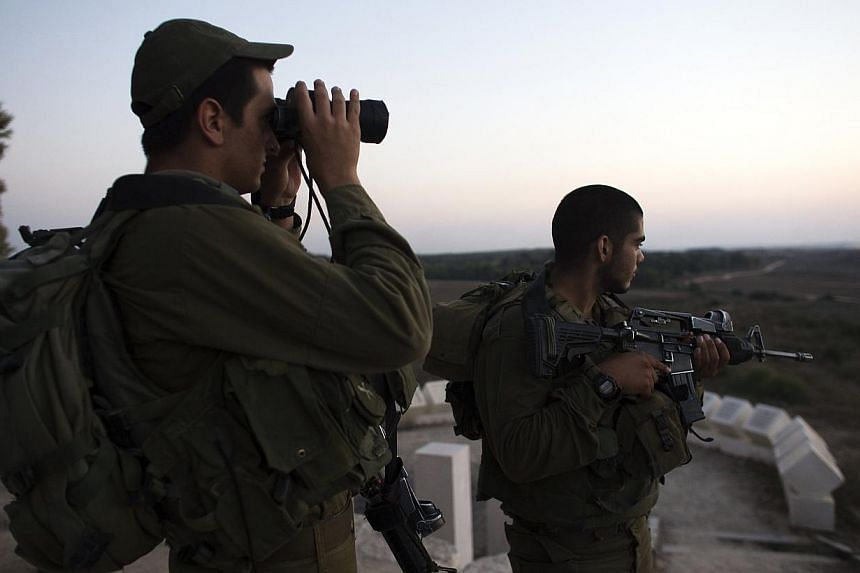 Israeli soldiers stand near the border with the Gaza Strip on July 26, 2014.The Israeli army said on Sunday, July 27, that it is resuming its raids on Gaza by land, sea and air after Hamas continued firing rockets, ending a unilateral 12-hour h