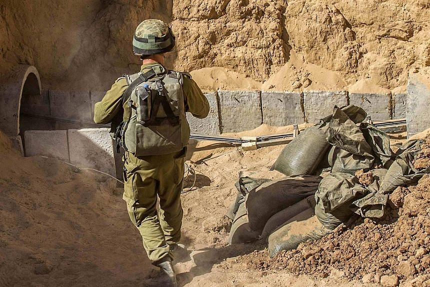 An Israeli army officer stands at the entrance of a tunnel said to be used by Palestinian militants for cross-border attacks, during an army organised tour for journalists on July 25, 2014.Egypt's army said Sunday, July 27 it has destroyed 13 m