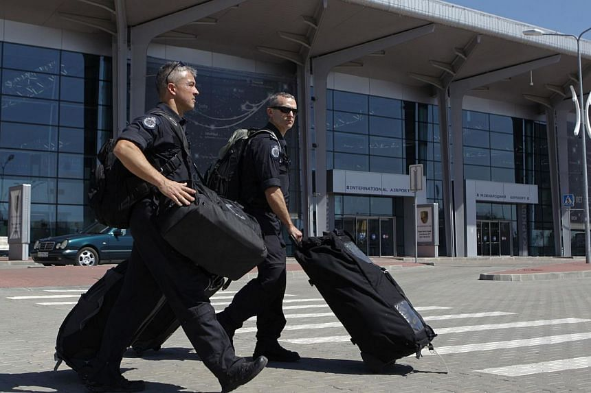 Members of the Australian police mission walk in front of the main terminal after arriving at Kharkiv airport, before proceeding to the crash site of Malaysia Airlines Flight MH17 on July 26, 2014. Australian Prime Minister Tony Abbott said his count