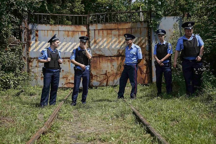 Ukrainian police stand guard at a railway entrance of the Kharkiv tank factory as they wait for a train carrying the remains of the victims of Malaysia Airlines flight MH17, in Kharkiv on July 22, 2014. Sixty-eight Malaysian police personnel wil