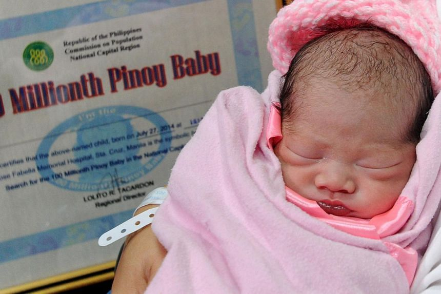 "Newly-born baby girl Jennalyn Sentino, who has been designated as the Philippines' ""100,000,000th baby"", sleeps during a presentation at a government hospital in Manila on July 27, 2014. -- PHOTO: AFP"