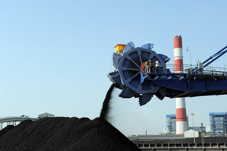 In this photograph taken on February 18, 2011, Indian workers use heavy machinery to sift through coal at the Adani Power company thermal power plant at Mundra, India, some 400km from Ahmedabad. Australia has approved a massive coal mine by Indi