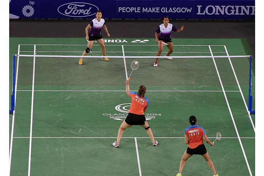 Singapore's Shinta Mulia Sari (top right) besides her doubles partner Lei Yao (top left) against India's Ashwini Ponnappa (bottom right) and Jwala Gutta (centre) in the Mixed Team event at the Emirates Arena at the 2014 Commonwealth Games in Glasgow