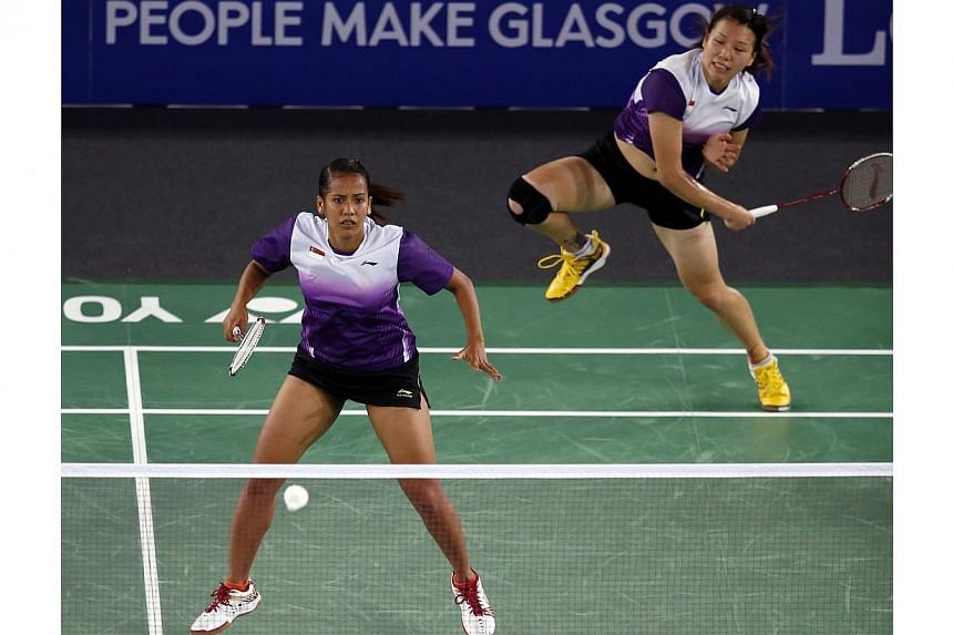 Singapore's Lei Yao (top right) plays a shot besides her doubles partner Shinta Mulia Sari (left) against India's Ashwini Ponnappa and Jwala Gutta (both not in picture) in the Mixed Team event at the Emirates Arena at the 2014 Commonwealth Games in G