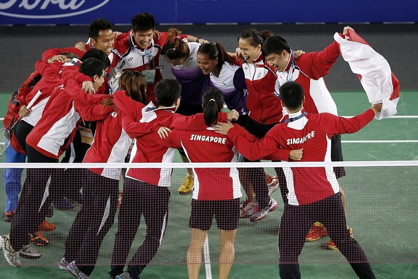 Singapore team members celebrate on the court after the women doubles pair of Lei Yao and Shinta Mulia Sari defeated India's Ashwini Ponnappa and Jwala Gutta (both not in picture) in the Mixed Team event at the Emirates Arena at the 2014 Commonwealth