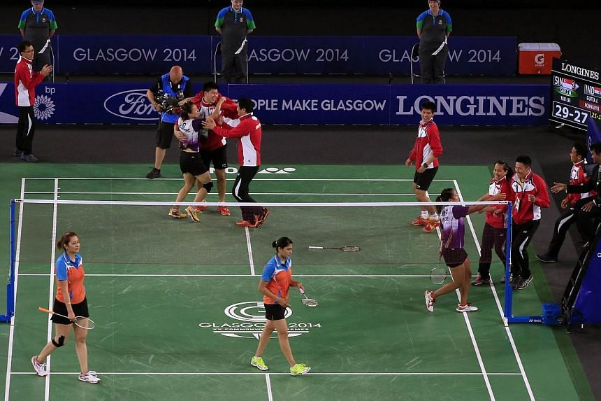 Singapore team members run to congratulate doubles pair of Lei Yao (centre top) and Shinta Mulia Sari (right) after the women defeated India's Ashwini Ponnappa (centre bottom) and Jwala Gutta (left) in the Mixed Team event at the Emirates Arena at th