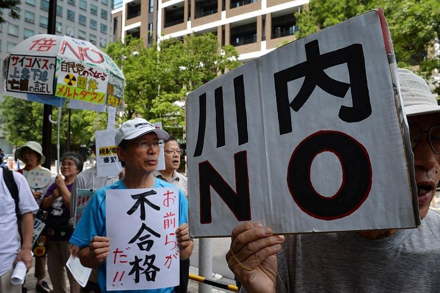 "An anti-nuclear protester holds a placard reading ""Sendai NO"", in reference to the Sendai Nuclear Power Plant in Kyushu, during a rally in Tokyo on July 16, 2014. Japanese officials are handing out radiation-blocking iodine tablets to people liv"