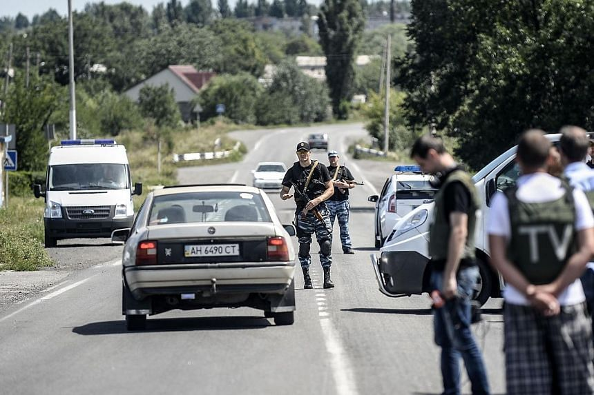 Pro-Russian militants block the way behind Dutch and Australian forensic teams on their way to the crash site of the Malaysia Airlines flight MH17 on Monday, July 28, 2014 in Donetsk. Dutch and Australian forensic investigators on their way to t