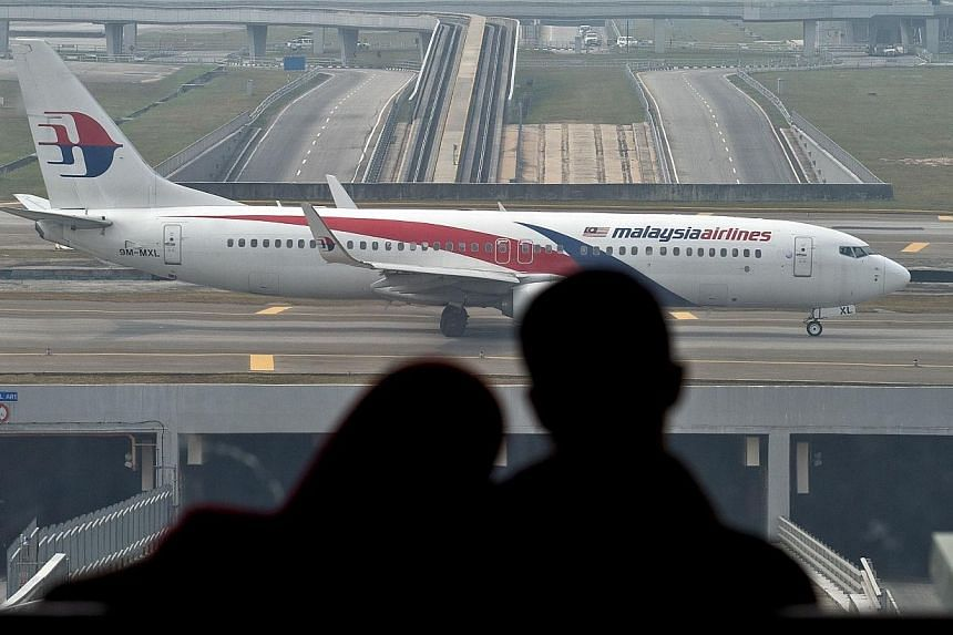 A couple watches the a Malaysia Airlines plane taxi on the runway at the Kuala Lumpur International Airport in Sepang on July 27, 2014.Malaysia Airlines, reeling under the pressure of two catastrophic aviation tragedies, is mulling a name chang