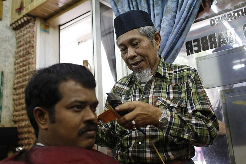 Above: Mr Mahmood Tamam, 63 (right), a long-time resident at Stirling Road, speaking to media representatives during a preview of the My Queenstown Heritage Trail yesterday. Left: Mr Kamsari Gari, 63, trimming the hair of Mr Mohamed Ani, 38, at Jali