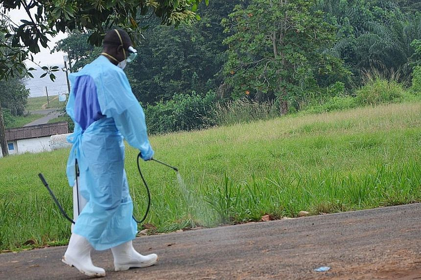 A picture taken on July 24, 2014 shows a staff member of the Christian charity Samaritan's Purse spraying product as he treats the premises outside the ELWA hospital in the Liberian capital Monrovia. The Liberian government on Sunday closed most