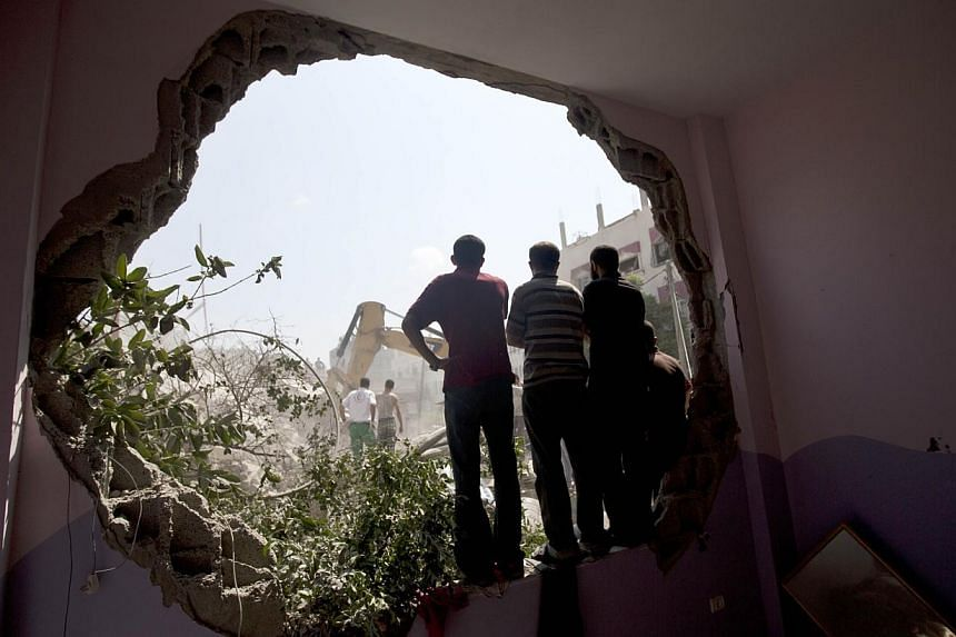 Palestinians stand watching from a whole in a wall as Civil Defence workers remove the rubble of a building destroyed in an Israeli air strike, in Gaza City, on July 21, 2014.The UN Security Council on Monday called for an immediate humanitaria