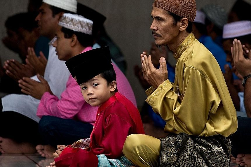 A Malaysian Muslim man offers prayers with his son at the national mosque in Kuala Lumpur on July 28, 2014.-- PHOTO: AFP