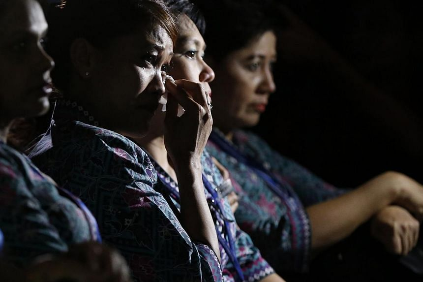 Malaysia Airlines flight attendants cry during a multi-faith event to pray for the passengers and crew of MH17 at the airline's academy in Kuala Lumpur, on July 25, 2014. -- PHOTO: REUTERS