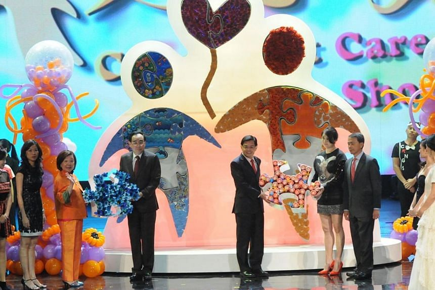 Education Minister Heng Swee Keat and ComChest Chairman Phillip Tan putting final touches to the first Care & Share art installation completed by celebrities, ComChest beneficiaries and the community. -- PHOTO:COMMUNITY CHEST