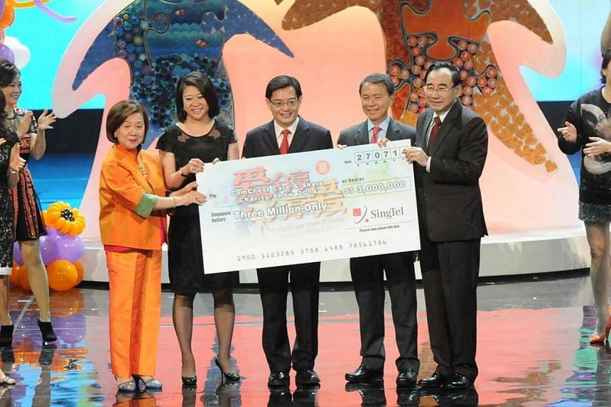 Ms Chua Sock Koong, Group chief executive of SingTel, presenting a cheque of $3 million to Community Chest at the ComChest Care & Share Charity Show 2014. -- PHOTO:COMMUNITY CHEST