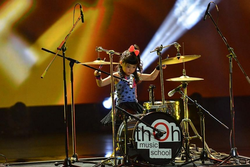 Six-year-old Oon Xyn, ComChest beneficiary from Eden Children's Centre (Simei), playing the drums alongside MediaCorp artistes Kym Ng and Jerry Yeo (not in photo) during ComChest Care & Share Charity Show 2014. --PHOTO:COMMUNITY CHEST