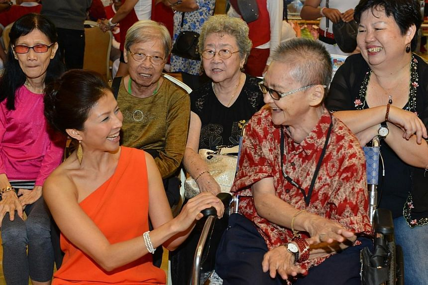 Wong Li-Lin, Community Chest Ambassador, interacting with elderly Community Chest beneficiaries during the ComChest Care & Share Charity Show 2014. -- PHOTO:COMMUNITY CHEST