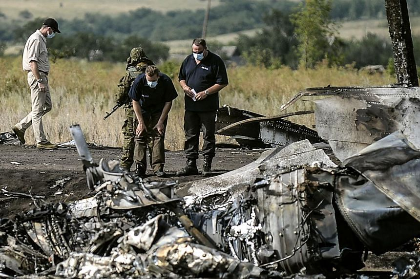 Investigators work at a the crash site of the Malaysia Airlines Flight MH17 near the village of Hrabove (Grabovo), some 80km east of Donetsk, on July 25, 2014.Black boxes recovered from downed Malaysia Airlines flight MH17 in rebel-held east Uk