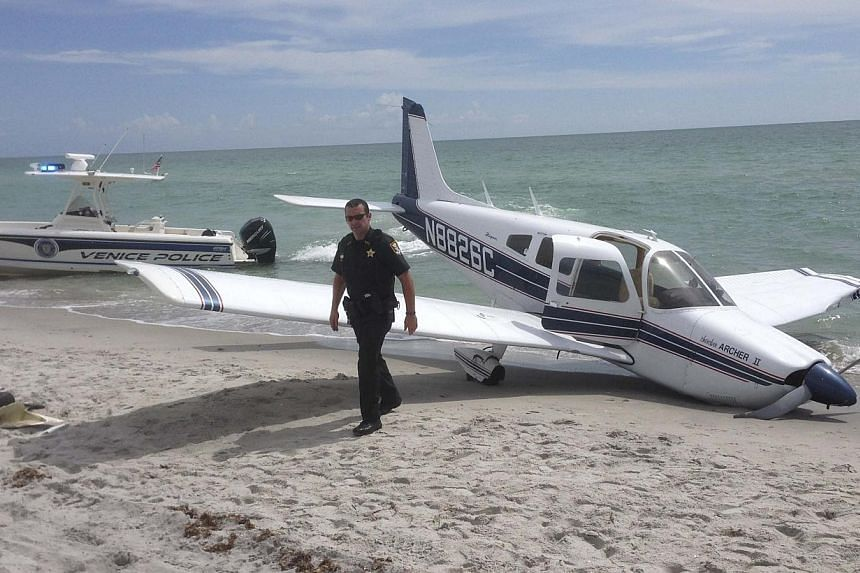 First responders respond at the scene of a single engine Piper Cherokee plane crash in this photo provided by the Sarasota County Sheriff's Office in Caspersen Beach in Venice, Florida on July 27, 2014. A small plane crash-landed on a beach in t