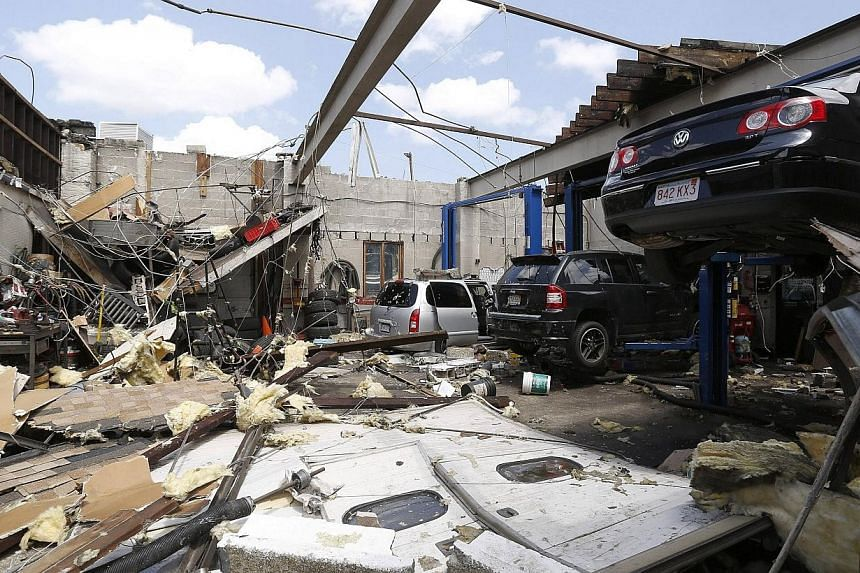 A collapsed roof is seen with damaged automobiles at a car workshop on Herman Street in Revere, Massachusetts, July 28, 2014.Officials and residents in the Boston-area city of Revere were picking up the pieces early on Tuesday after it was rake