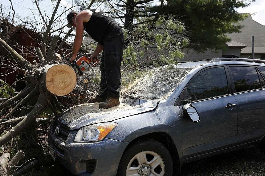 A worker cuts a tree from on top of a storm-damaged car on Beach Street in Revere, Massachusetts, July 28, 2014.Officials and residents in the Boston-area city of Revere were picking up the pieces early on Tuesday after it was raked by a rare t