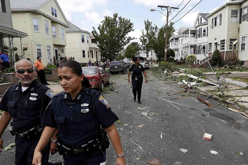 Boston Police Department officers investigate storm damage along Taft Street in Revere, Massachusetts, July 28, 2014.Officials and residents in the Boston-area city of Revere were picking up the pieces early on Tuesday after it was raked by a r