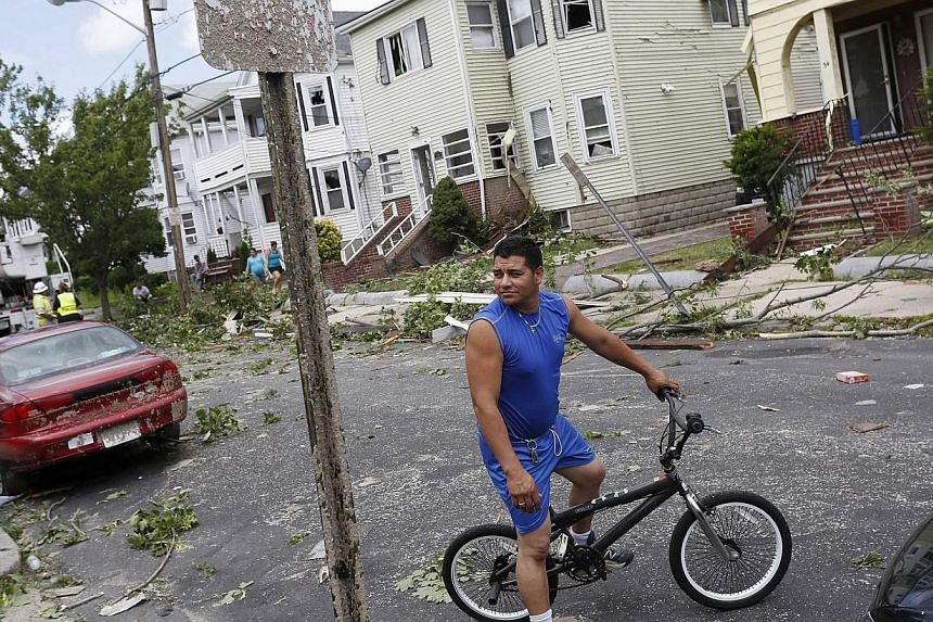 A man tours the storm damage by bicycle on Taft Street in Revere, Massachusetts, July 28, 2014.Officials and residents in the Boston-area city of Revere were picking up the pieces early on Tuesday after it was raked by a rare tornado that knock