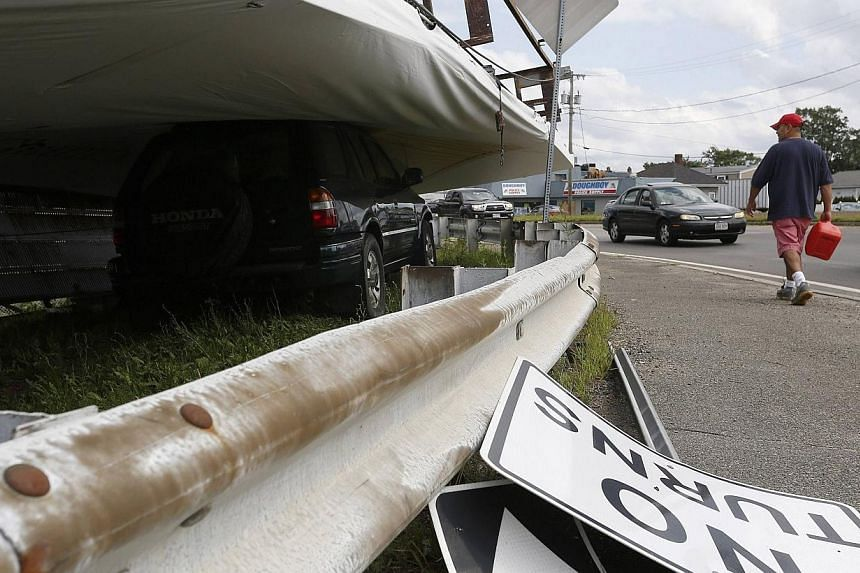 A man carries a gas can past a sport-utility vehicle (SUV) lying beneath a billboard toppled by a storm, along Route 60 in Revere, Massachusetts, July 28, 2014.Officials and residents in the Boston-area city of Revere were picking up the pieces