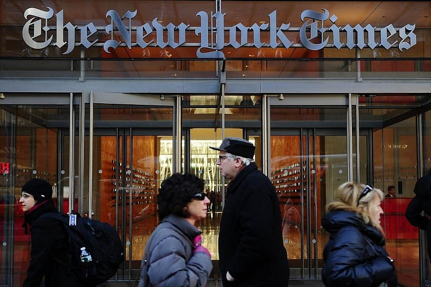 People walk by the entrance to US newspaper The New York Times in New York in this March 8, 2011 file photo.US daily newspapers slashed some 1,300 jobs in 2013, extending the steady declines over the past decade, a survey showed Tuesday. -- PHO