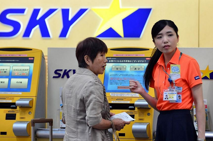 A ground staff (right) of Japan's Skymark Airlines guides a customer at the self check-in counter of Skymark Airlines at Haneda airport in Tokyo on July 29, 2014.Airbus on Tuesday said it has cancelled a US$2.2 billion (S$ 2.7 billion) deal wit