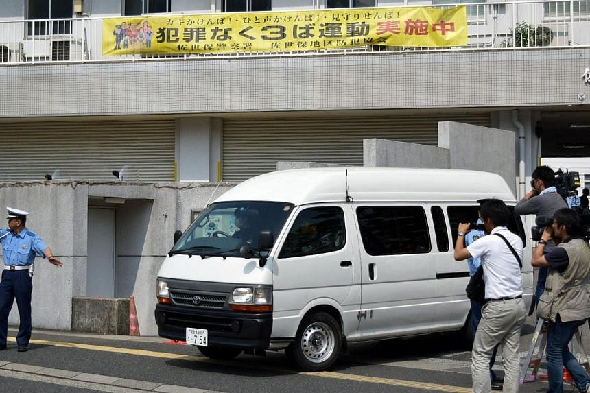 A van carrying a 15-year-old high schoolgirl, who was arrested on suspicion of killing a school friend at her home, leaves a police station for the prosecutor's office in Sasebo in Nagasaki prefecture, on Japan's southern island of Kyushu on July 28,