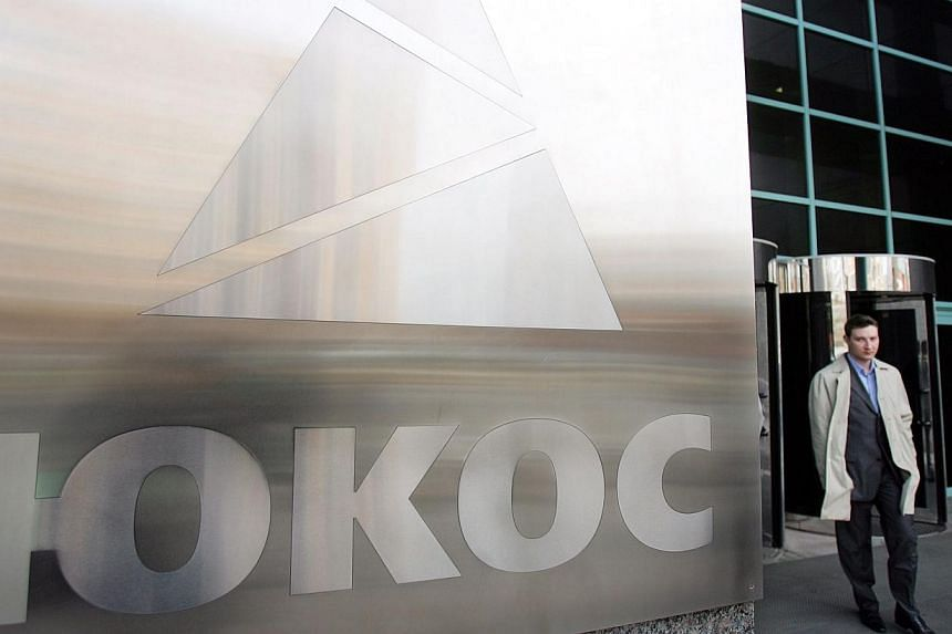 A file photo taken on April 4, 2007 shows a man walking next to the logo of oil giant Yukos at the Moscow headquarters.An international court ordered Russia on Monday to pay Yukos shareholders a record US$50 billion (S$62 billion) compensation