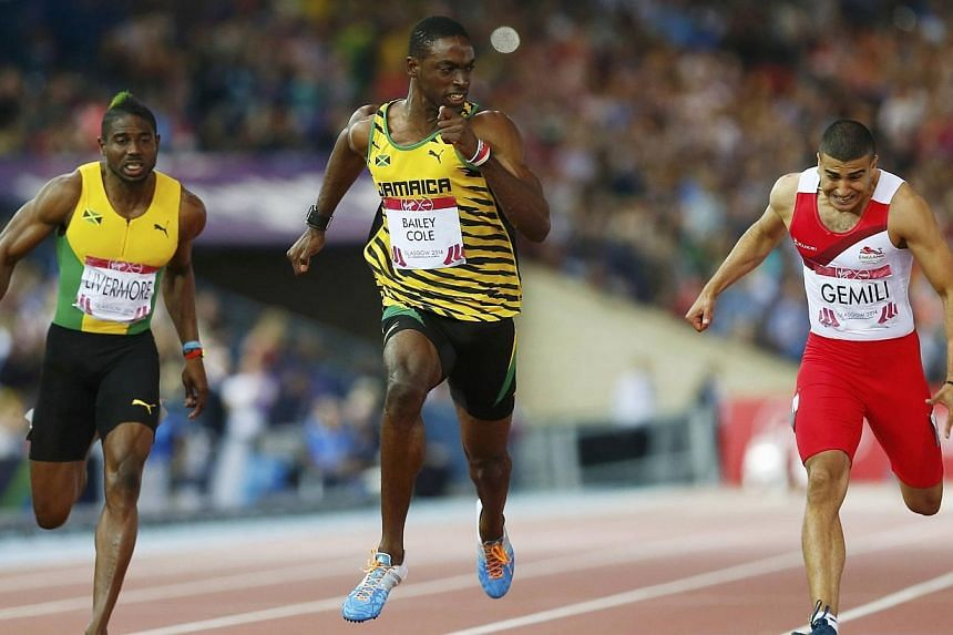 Kemar Bailey-Cole (centre) of Jamaica finishes first place ahead of Adam Gemili (right) of England, and Jason Livermore of Jamaica during the men's 100m final at the 2014 Commonwealth Games in Glasgow, Scotland, on July 28, 2014. Kemar Bailey-Co