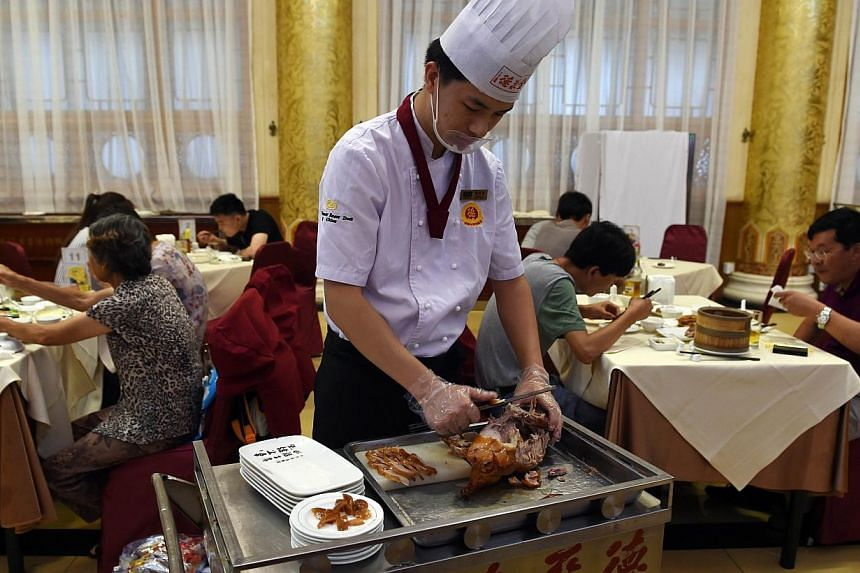 A chef slicing Peking Duck for diners at the Quanjude restaurant in Beijing in July.-- PHOTO: AFP