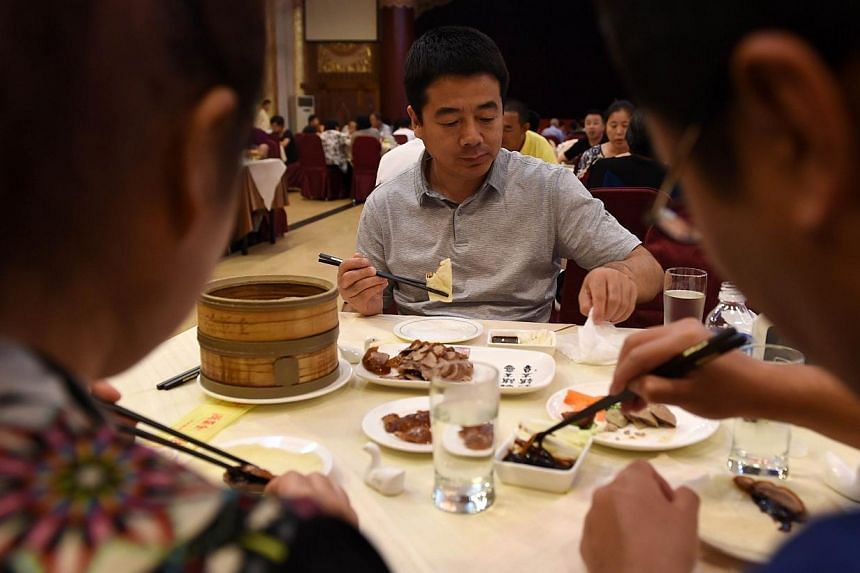 Diners tucking in to Peking Duck at the Quanjude restaurant in Beijing in July. -- PHOTO: AFP
